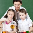 Little pupils pour chemical liquids in different flasks — Stock Photo