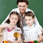 Little pupils pour chemical liquids in different flasks — Stock Photo #12287840