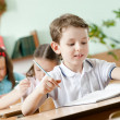 Schoolboy does some notes on the sheet of paper — Stock Photo