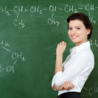 Smiley teacher hands chalk standing at the blackboard — Stock Photo #12287983