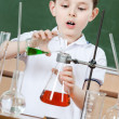 Little chemist pours colored liquid in conical flask — Stockfoto