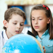 Two friends examine a school globe — Stock Photo #12288120