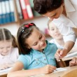 Teacher helps pupils to do the task — Stock Photo