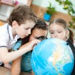Three friends examine school globe — Stock Photo #12288207