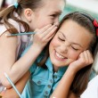 Two schoolgirls whisper to each other — Stock Photo