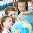 Classmates help to each other to find something at the globe — Stock Photo