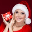 Photo: Attractive woman in Christmas cap hands a present
