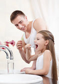 Father teachers his daughter to clean teeth — Stock Photo
