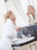 Pretty woman creams her face in bathroom — Stock Photo