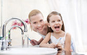 Little girl brushes teeth with her mother — Stock Photo