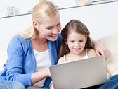 Little child surfs on the internet with her mother — Stock Photo