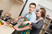 Man in striped apron cuts vegetables for dinner — Stock Photo