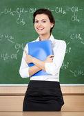 Laughing teacher at the blackboard hands a folder — Stock Photo