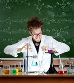 Laughing mad professor combines some liquids — Stock Photo