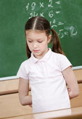 Schoolgirl doesn't know the answer and puts her hands behind the back — Stockfoto
