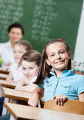 Smiley schoolgirl sits at the desk — Stock Photo