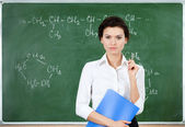 Serious teacher stands at the blackboard while holding notebook — Stock Photo