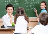Teacher questions pupils at mathematics — Stock Photo
