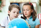 Two friends examine a school globe — Stock Photo