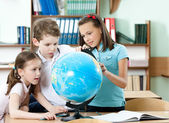 Pupils find something at the school globe — Stok fotoğraf