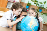 Three friends examine a school globe — Stock Photo