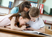 Pupils watch something through the magnifying glass — Stock Photo