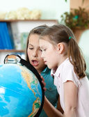 Pupils look at the globe in wide-eyed astonishment — Stok fotoğraf
