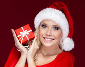 Attractive woman in Christmas cap hands a present — Stock Photo