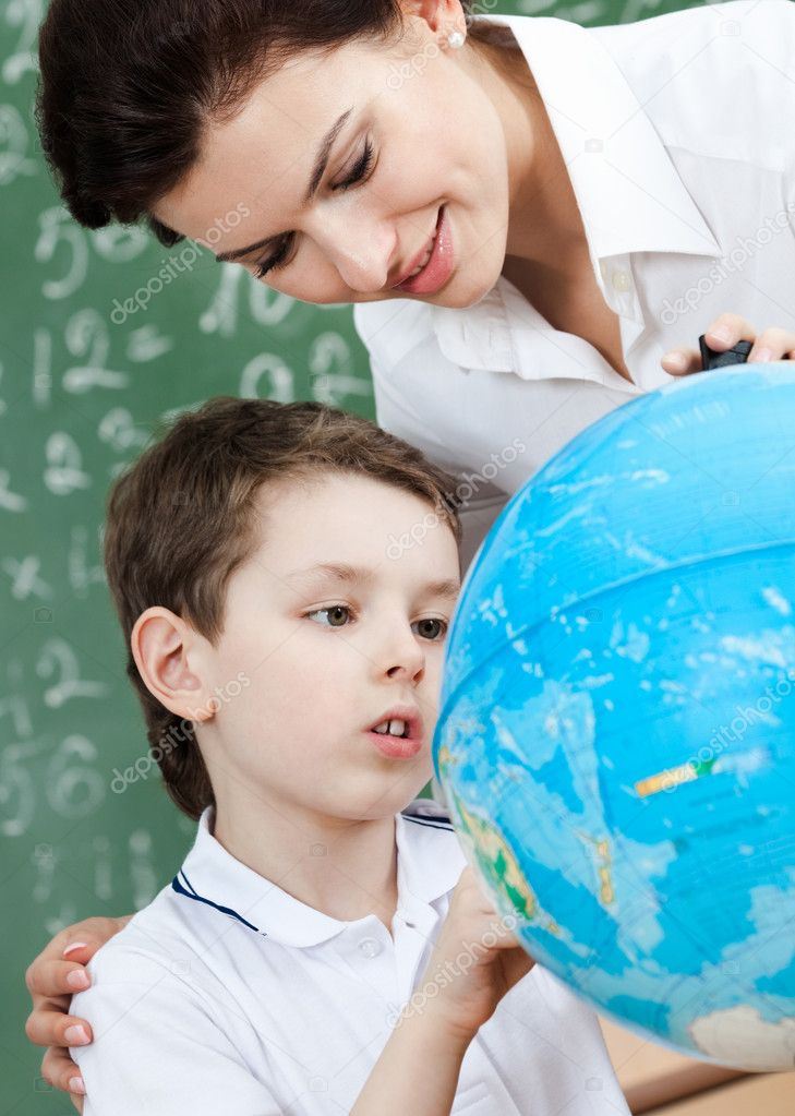 Little schoolboy uses terrestrial globe while studying geography  Stock Photo #12287351