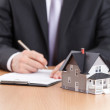 Businessman signs contract behind home architectural model — Stock Photo