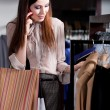 Speaking on the cellphone and choosing clothes in the store — Stock Photo