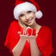 Royalty-Free Stock Photo: Attractive girl in Christmas cap hands a present