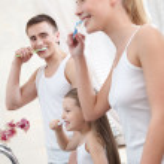 Family of three brush their teeth — Stock Photo #12417904