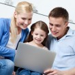 Happy family sit on the sofa with laptop — Stock Photo