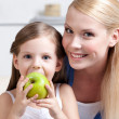 Smiley mom with her eating apple daughter — Stock Photo