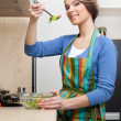 Attractive woman in striped apron cooks vegetables — Stock Photo #12418409