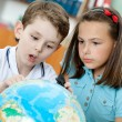 Two pupils look at the globe — Stock Photo