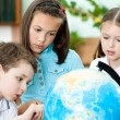 Постер, плакат: Pupils stare at the school globe