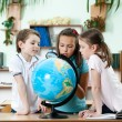 Friends stare at school globe — Stock fotografie #12418943