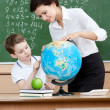 Постер, плакат: Geography teacher shows something to the pupil at the globe