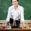Stock Photo: Smiley chemistry teacher is surrounded with chemical instruments