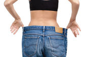 Body of a slim girl wearing enormous jeans — Stock Photo