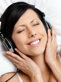 Woman in brassiere listens to music — Stock Photo