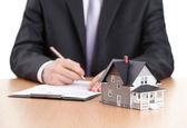 Işadamı işaretler sözleşme arkasında ev mimari modeli — Stok fotoğraf