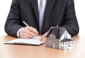Uomo d'affari segni contratto dietro modello architettonico casa — Foto Stock