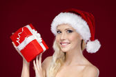 Beautiful woman in Christmas cap hands present — Stock Photo