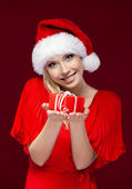 Attractive girl in Christmas cap hands a present — Stock Photo