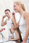 Family of three brush their teeth — Stock Photo