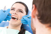Dentist examines the oral cavity of a pretty patient — Stock Photo