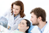 The patient examines the x ray photo of her teeth — Stock Photo